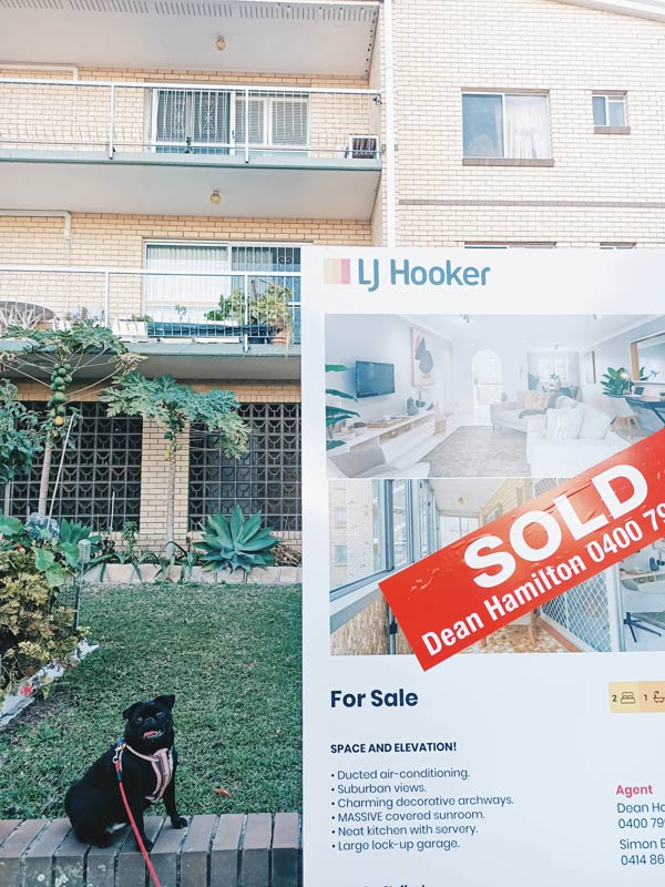First home buyer's new property, with sold sign and pet dog